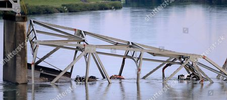 Partially-submerged vehicles lie in the debris of the collapsed portion of the Interstate 5 bridge in the Skagit River, in Mount Vernon, Wash. A truck carrying an oversize load struck the four-lane bridge on the major thoroughfare between Seattle and Canada, sending a section of the span and two vehicles into the Skagit River below Thursday evening. All three occupants suffered only minor injuries. At an overnight news conference, Washington State Patrol Chief John Batiste blamed the collapse on a tractor-trailer carrying a tall load that hit an upper part of the span