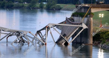A collapsed portion of the Interstate 5 bridge lies at the Skagit River, in Mount Vernon, Wash. A truck carrying an oversize load struck the four-lane bridge on the major thoroughfare between Seattle and Canada, sending a section of the span and two vehicles into the Skagit River below Thursday evening. All three occupants suffered only minor injuries. At an overnight news conference, Washington State Patrol Chief John Batiste blamed the collapse on a tractor-trailer carrying a tall load that hit an upper part of the span