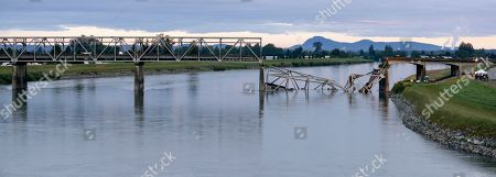 The north end of the Interstate 5 bridge crossing the Skagit River lies collapsed in the water, in Mount Vernon, Wash. A truck carrying an oversize load struck the four-lane bridge on the major thoroughfare between Seattle and Canada, sending a section of the span and two vehicles into the Skagit River below Thursday evening. All three occupants suffered only minor injuries. At an overnight news conference, Washington State Patrol Chief John Batiste blamed the collapse on a tractor-trailer carrying a tall load that hit an upper part of the span