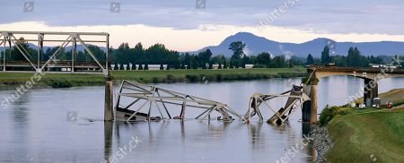 A collapsed portion of the Interstate 5 bridge lies in the Skagit River, in Mount Vernon, Wash. A truck carrying an oversize load struck the four-lane bridge on the major thoroughfare between Seattle and Canada, sending a section of the span and two vehicles into the Skagit River below Thursday evening. All three occupants suffered only minor injuries. At an overnight news conference, Washington State Patrol Chief John Batiste blamed the collapse on a tractor-trailer carrying a tall load that hit an upper part of the span