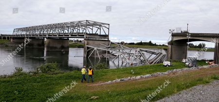 Workers walk past the collapsed portion of the Interstate 5 bridge at the Skagit River, in Mount Vernon, Wash. A truck carrying an oversize load struck the four-lane bridge on the major thoroughfare between Seattle and Canada, sending a section of the span and two vehicles into the Skagit River below Thursday evening. All three occupants suffered only minor injuries. At an overnight news conference, Washington State Patrol Chief John Batiste blamed the collapse on a tractor-trailer carrying a tall load that hit an upper part of the span