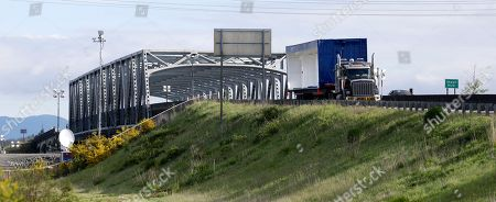 A truck carrying an oversize load sits parked southbound on Interstate 5 south of the collapsed portion of the highway bridge, seen behind at left, at the Skagit River, in Mount Vernon, Wash. The truck struck the four-lane bridge on the major thoroughfare between Seattle and Canada Thursday evening, sending a section of the span and two vehicles into the Skagit River. All three occupants suffered only minor injuries. At an overnight news conference, Washington State Patrol Chief John Batiste blamed the collapse on a tractor-trailer carrying a tall load that hit an upper part of the span