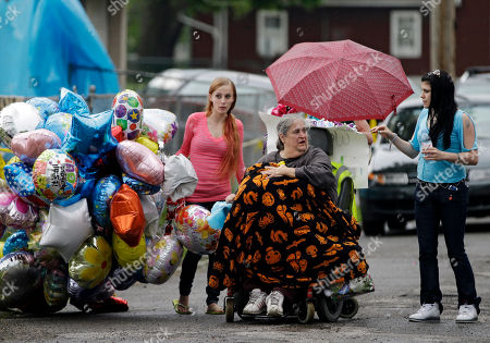 Deborah Knight, center, grandmother of Michelle Knight, drives her wheelchair past the home of Gina DeJesus in Cleveland. Ariel Castro, 53, serving a life sentence for the kidnapping and rape of Knight and two other women, was found hanging in his cell, Tuesday night, Sept. 3, 2013, at the Correctional Reception Center in Orient, Ohio