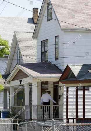 A law enforcement officer checks the front door of the house where three women missing for about a decade were found alive, in Cleveland, . Ariel Castro was charged with kidnapping and rape while his brothers, Pedro and Onil Castro, were arrested and cleared without charges