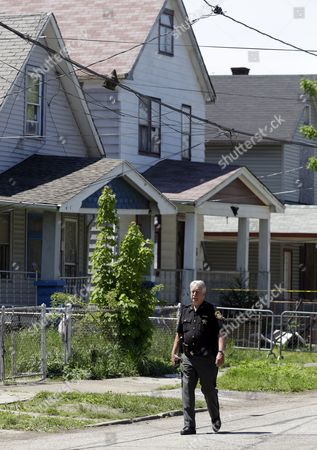 Stock Image of A law enforcement officer walks past the house where three women missing for about a decade were found alive, in Cleveland, . Ariel Castro was charged with kidnapping and rape while his brothers, Pedro and Onil Castro, were arrested and cleared without charges