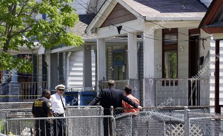 Law enforcement officers talk in front of the house where three women missing for about a decade were found alive, in Cleveland, . Ariel Castro was charged with kidnapping and rape while his brothers, Pedro and Onil Castro, were arrested and cleared without charges