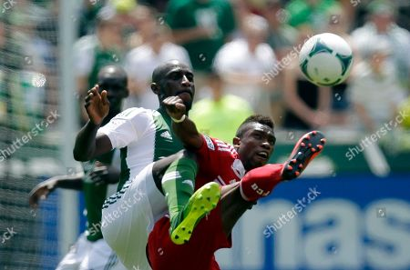 Fabian Castillo, Frederic Piquionne FC Dallas midfielder Fabian Castillo, right, kicks the ball away from Portland Timbers forward Frederic Piquionne during the first half of an MLS soccer game in Portland, Ore