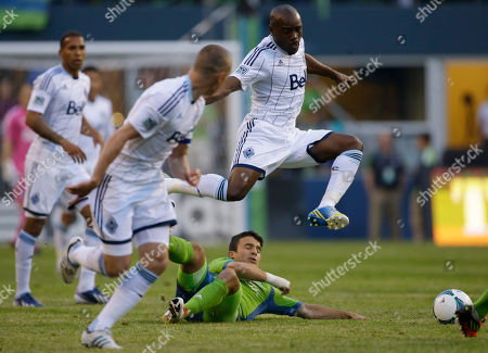 Servando Carrasco, Nigel Reo-Coker Seattle Sounders' Servando Carrasco goes down, as Vancouver Whitecaps' Nigel Reo-Coker leaps over him in the first half of an MLS soccer match, in Seattle