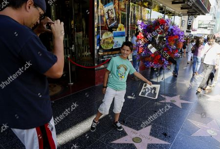 Darron Quigley,left, takes a photo of his son Jack Quigley, 8, from Simi Valley, Calif., in front of flowers placed on the Hollywood Walk of Fame star of Ray Manzarek of The Doors today, in Los Angeles Monday, May 20, 2013. Ray Manzarek, the keyboardist and founding member of The Doors who had a dramatic impact on rock 'n' roll, has died. He was 74