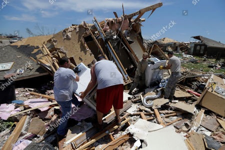 From left, Charles Hogan, from left, and Chris Gregg, help U.S. Air Force Staff Sgt. Alexander Frew, and Staff Sgt. Dominic Salierno, both based at nearby Tinker Air Force Base, recover the dryer and washing machine of Jennifer Walker from her damaged home in Moore, Okla
