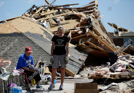 """In Moore, Okla, Jennifer Walker, left, sifts through a memories book as she and her friend Kate Burger, center, stand in front of what remains of Walker's home. When she moved into her single-story brick house in Moore eight years ago, she considered installing a safe room or bunker to shield her family. She decided against it. This week as she stood in the rubble and watched two National Guardsmen dig through the wreckage of her home to retrieve her two-week-old washer and dryer, she made a vow: She'll build an underground bunker, even if she has to shell out $10,000. """"Oh yeah, I would forego the granite, whirlpool tub,"""" she says. """"I would forego all that just to have the shelter, for sure. Now"""