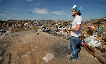 Cody Cannon looks at tornado destruction in his neighborhood from the second floor of his parent's home that once was his bedroom, in Moore, Okla. Cleanup continues two days after a huge tornado roared through the Oklahoma City suburb, flattening a wide swath of homes and businesses