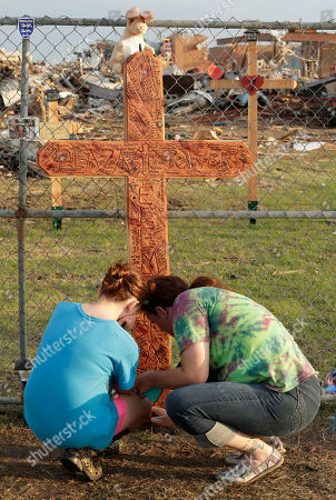 Kaitlyn Campbell, 12, and her mother Rachel Holder sign a cross at a makeshift memorial outside Plaza Towers Elementary School where Campbell is in fifth grade, in Moore, Okla. Campbell took shelter in a bathroom to survive Monday's tornado which destroyed the school killing seven students an devastated a large swath of the Oklahoma City suburb