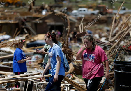 Crissy Gregg, left, leads Morgan Gregg, right, through a debris field as they help their relative Jennifer Walker, left rear, recover items from her tornado-damaged home, in Moore, Okla. Cleanup continues two days after a huge tornado roared through the Oklahoma City suburb, flattening a wide swath of homes and businesses