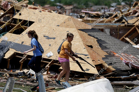 Crissy Gregg, left, and Lauren Hogan, carrying air rifles, help their relative Jennifer Walker, not pictured, recover items from her tornado damaged home, in Moore, Okla. Cleanup continues two days after a huge tornado roared through the Oklahoma City suburb, flattening a wide swath of homes and businesses