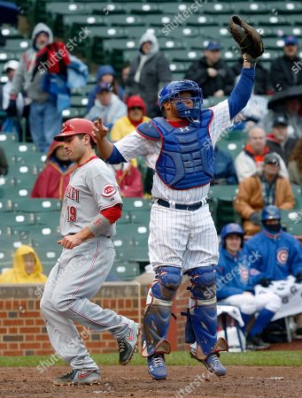 Joey Votto, Welington Castillo Cincinnati Reds' Joey Votto, left, scores past Chicago Cubs catcher Welington Castillo on a double by Jay Bruce during the sixth inning of a baseball game, in Chicago