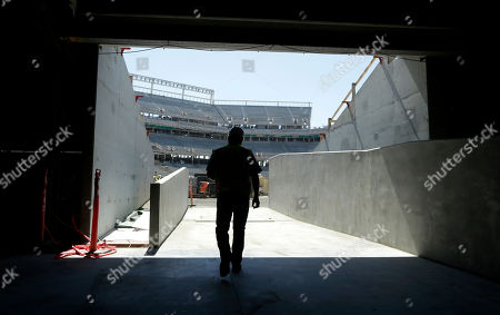 San Francisco 49ers project executive Jack Hill walks in a tunnel walking toward the field at the new San Francisco 49ers football stadium in Santa Clara, Calif. Goodbye grungy, cold Candlestick Park. Hello high tech, glittering, Levi's Stadium. Fifty-four years after $32 million Candlestick Park opened, the 49ers are building a new $1.2 billion showcase of a stadium which is almost twice as big, wired to the hilt, and opening its doors just in time to host Super Bowl 50 in the heart of the Silicon Valley