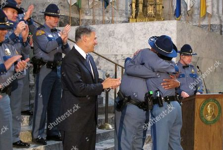 Wash. Gov. Jay Inslee, left front, smiles as Washington State Patrol Chief John Batiste hugs his daughter, Johnna Batiste, after she was sworn in and presented her commission card during a Washington State Patrol Academy graduation in the Capitol rotunda,, in Olympia, Wash. The 27 graduating troopers received more than 1,000 hours of training