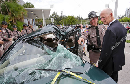 Stock Image of Rick Scott, Joe Sanchez Florida Highway Patrol Public Affairs Officer Joe Sanchez, second from right, shows Gov. Rick Scott a car that was recently involved in a fatal accident that is now being displayed in front of the Alonzo and Tracy Mourning Senior High School, in North Miami, Fla. Scott spoke to students at the school before signing a statewide ban on texting while driving into law. The law makes reading or sending a text, emailing and instant messaging on smart phones while driving a secondary offense, meaning police have to first stop drivers for another offense like an illegal turn