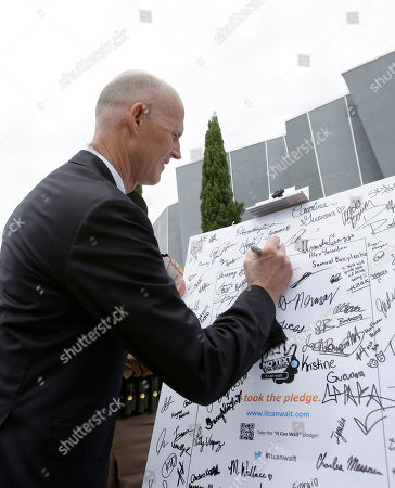 Stock Photo of Rick Scott Florida Gov. Rick Scott signs a pledge to not text and drive on a poster in front of the Alonzo and Tracy Mourning Senior High School, in North Miami, Fla. Scott spoke to students at the school before signing a statewide ban on texting while driving into law. The law makes reading or sending a text, emailing and instant messaging on smart phones while driving a secondary offense, meaning police have to first stop drivers for another offense like an illegal turn