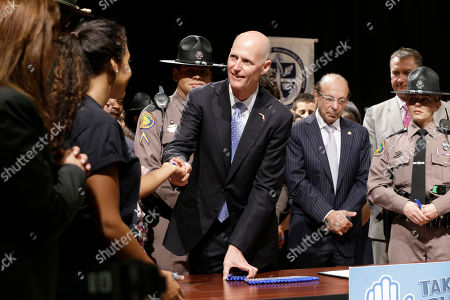 Stock Picture of Rick Scott Florida Gov. Rick Scott, center, hands out markers to students after he signed a statewide ban on texting while driving into law during a ceremony, at the Alonzo and Tracy Mourning Senior High School in North Miami, Fla. The law makes Florida the 40th state to enact a texting-while-driving ban for all drivers