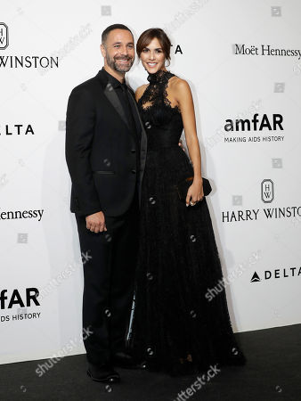 Italian actor Raul Bova, left, with his girlfriend Rocio Munoz Morales pose for photographers as they arrives for the amfAR charity dinner during the fashion week in Milan, Italy
