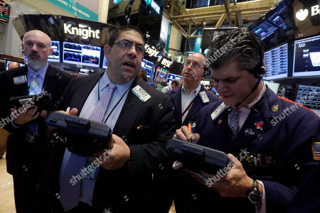Robert Osborne Trader Robert Osborne, second left, works on the floor of the New York Stock Exchange, . Stocks are heading slightly lower in early trading after the government reported that Americans cut back on their spending last month, a discouraging sign for the economy