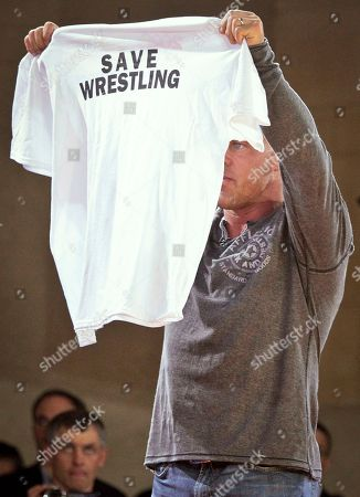 """Former Olympic gold medalist and professional wrestler Kurt Angle holds up a T-shirt during a three-nation wrestling exhibition at Grand Central Terminal, in New York. The event dubbed """"The Rumble on the Rails"""" marked the fourth straight year a New York City landmark was transformed into a wrestling meet to raise money for charity, with the last two in Times Square. In February, the International Olympic Committee recommended that the sport be dropped starting with the 2020 Games"""