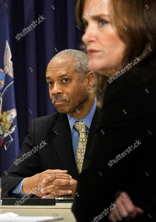 Bronx District Attorney Robert Johnson, left, and Nassau County D.A. Kathleen Rice, right, listen during a press conference on in New York. Members of the District Attorneys Association joined Gov. Cuomo as he proposed legislation to give prosecutors more power to combat public corruption, and will for the first time require public officials to report corrupt actions by their colleagues