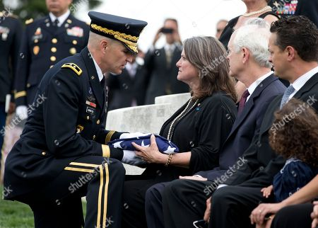 Barbara Broyles, Michael Linnington Barbara Broyles, center, the daughter of Army Lt. Col. Don C. Faith Jr., is handed the flag that draped her father's casket by Maj. Gen. Michael Linnington, left, during a burial ceremony, at Arlington National Cemetery in Arlington, Va