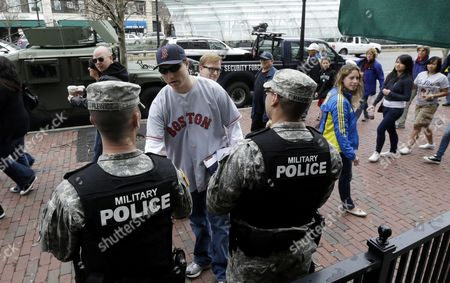 A man, center, shakes the hand of Spc. Adam Filewicz, center left, as Pvt. 1st Class Mark Mahoney, right, looks on at Kenmore Square in Boston on . Police captured Dzhokhar Tsarnaev, 19, the surviving Boston Marathon bombing suspect, in a backyard boat, Friday evening, after a wild car chase and gun battle earlier in the day left his older brother dead