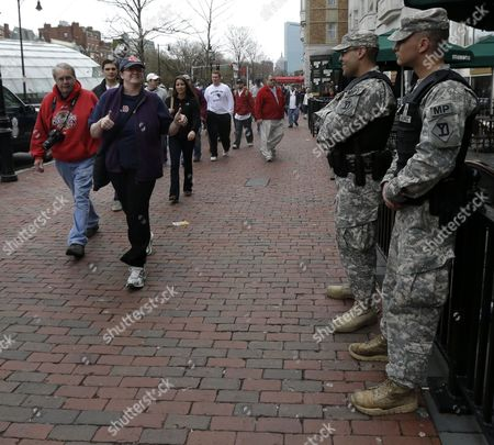 A woman, second from left, gestures at Spc. Adam Filewicz, right, and Pvt. 1st Class Mark Mahoney, second from right, at Kenmore Square, in Boston. Police captured Dzhokhar Tsarnaev, 19, the surviving Boston Marathon bombing suspect, in a backyard boat, Friday evening, after a wild car chase and gun battle earlier in the day left his older brother dead