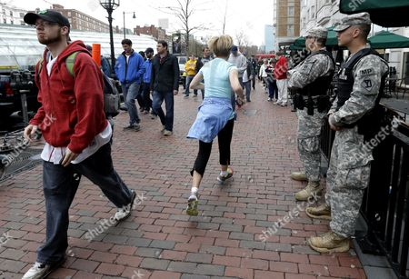 A jogger trots through a crowd as Spc. Adam Filewicz, right, and Pvt. 1st Class Mark Mahoney, second from right, stand guard at Kenmore Square, in Boston. Police captured Dzhokhar Tsarnaev, 19, the surviving Boston Marathon bombing suspect, in a backyard boat, Friday evening, after a wild car chase and gun battle earlier in the day left his older brother dead