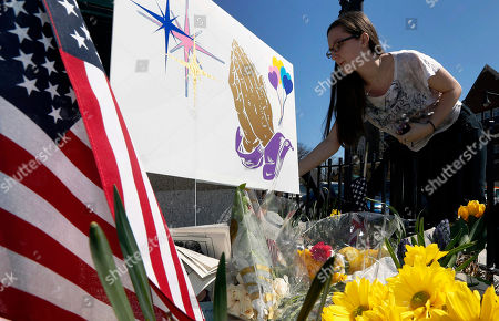 Shannon Walsh, 15, places flowers on a memorial to Boston Marathon bombing victim, Martin Richard, 8, near the Richard family house in the Dorchester neighborhood of Boston