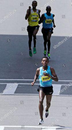Stock Photo of Lelisa Desisa, Micah Kogo, Gebregziabher Gebremariam Lelisa Desisa, of Ethiopia, pulls away from Gebregziabher Gebremariam, rear left, and Micah Kogo, of Kenya, during the final block of the 2013 running of the Boston Marathon in Boston, . Desisa won the race, with Kogo second and Gebremariam third