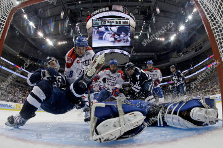 Josh Balch, Connor Hellebuyck, Jake Suter Yale's Josh Balch, left, is checked to the ice by UMass Lowell defenseman Jake Suter (28) as goalie Connor Hellebuyck (37) makes a sprawling save during the first period of an NCAA college hockey Frozen Four semifinal tournament game in Pittsburgh, . Yale won in overtime 3-2
