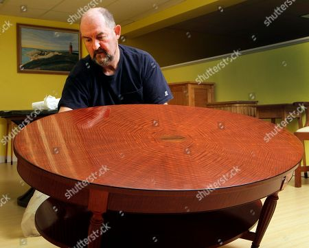 """Master Furniture Maker Terry Moore polishes a table, in Franklin, N.H. The table Moore made will join furniture made by state prison inmates at the opening of the """"Behind the Walls Craft Exhibition"""" at Grevior's Furniture store"""