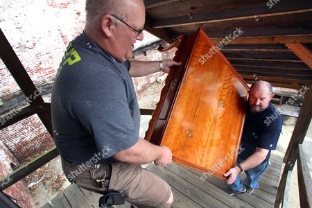 """New Hampshire State Prison shop supervisor John Limoge, left, and master furniture maker Terry Moore carry a table into Grevior's Furniture store in Franklin, N.H. The furniture, made by inmates at the state prison, will open the """"Behind the Walls Craft Exhibition"""" this weekend"""