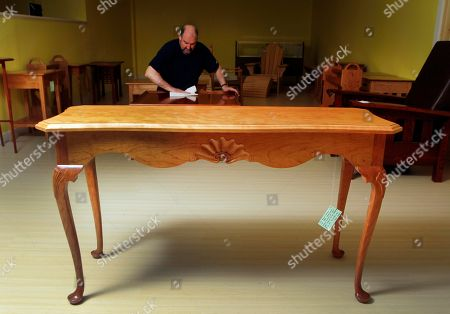 """A table made by New Hampshire state prison inmate Eric Grant is seen as Master Furniture Maker Terry Moore polishes another table, in Franklin, N.H. Furniture made from inmates at the state prison will open the """"Behind the Walls Craft Exhibition"""" at Grevior's Furniture store this weekend"""