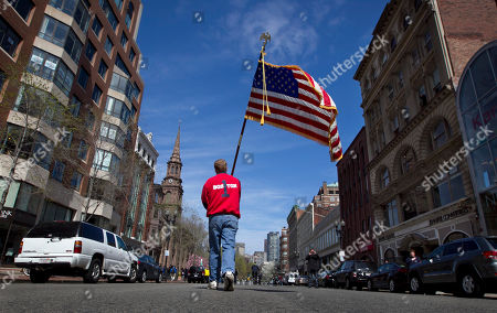 Mike Murphy Lt. Mike Murphy of the Newton, Mass., fire dept., carries an American flag down the middle of Boylston Street after observing a moment of silence in honor of the victims of the bombing at the Boston Marathon near the race finish line, in Boston, Mass