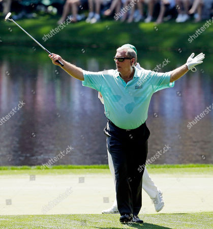 Fuzzy Zoeller acknowledges applauds after putting on the eighth hole during the par three competition before the Masters golf tournament, in Augusta, Ga