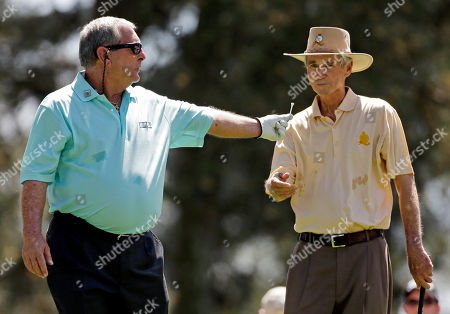Fuzzy Zoeller hands a tee to Hubert Green after teeing off on the first hole during the par three competition before the Masters golf tournament, in Augusta, Ga