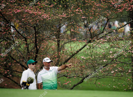 Stewart Cink talks with his caddie Matthew Hall before playing his second shot on the second hole during the first round of the Masters golf tournament, in Augusta, Ga