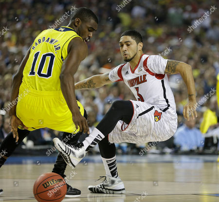 Louisville guard Peyton Siva (3) and Michigan guard Tim Hardaway Jr. (10) vie for a loose ball during the first half of the NCAA Final Four tournament college basketball championship game, in Atlanta