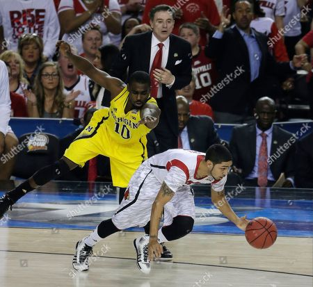 Louisville guard Peyton Siva (3) moves the ball against Michigan guard Tim Hardaway Jr. (10)during the first half of the NCAA Final Four tournament college basketball championship game, in Atlanta