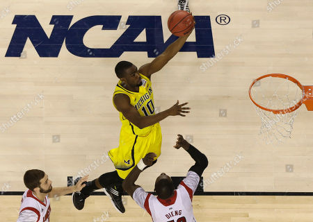 Michigan guard Tim Hardaway Jr. (10) heads to the hoop as Louisville center Gorgui Dieng (10) defends during the second half of the NCAA Final Four tournament college basketball championship game, in Atlanta