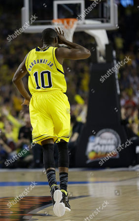 Michigan guard Tim Hardaway Jr. (10) reacts to a 3-point shot against the Louisville during the first half of the NCAA Final Four tournament college basketball championship game, in Atlanta