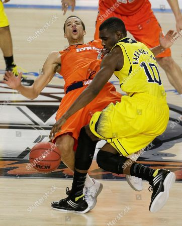 Syracuse's Michael Carter-Williams (1) falls to the court as Michigan's Tim Hardaway Jr. (10) vies for the ball during the second half of the NCAA Final Four tournament college basketball semifinal game, in Atlanta