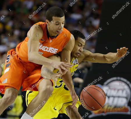 Syracuse's Michael Carter-Williams (1) and Michigan's Trey Burke (3) vie for a loose ball during the first half of the NCAA Final Four tournament college basketball semifinal game, in Atlanta
