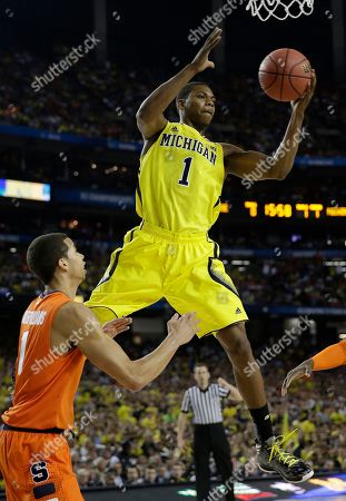 Michigan's Glenn Robinson III (1) recovers a loose ball as Syracuse's Michael Carter-Williams (1) defends during the first half of the NCAA Final Four tournament college basketball semifinal game, in Atlanta
